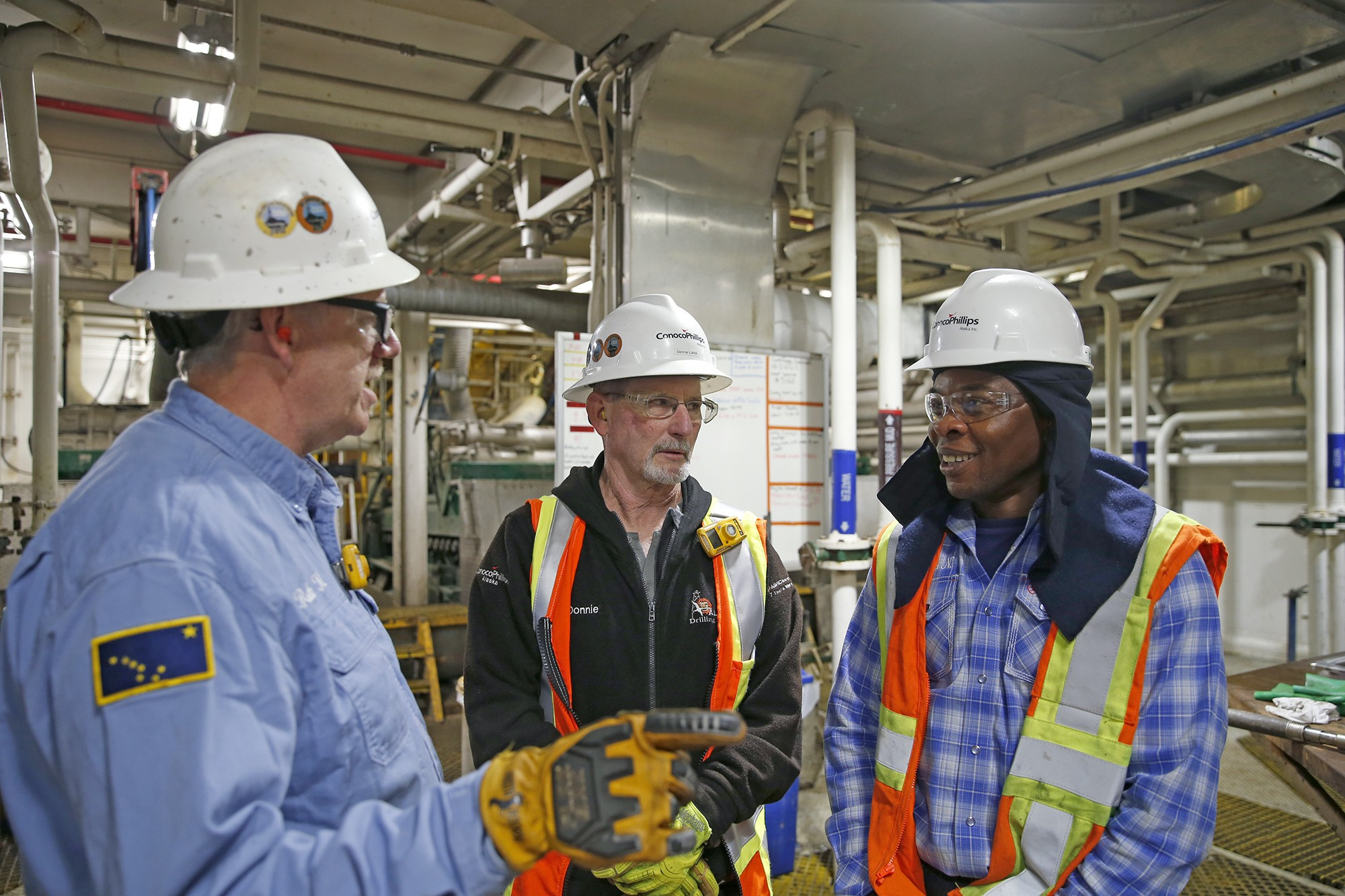3 men in safety gear having conversation indoors with pipes in background