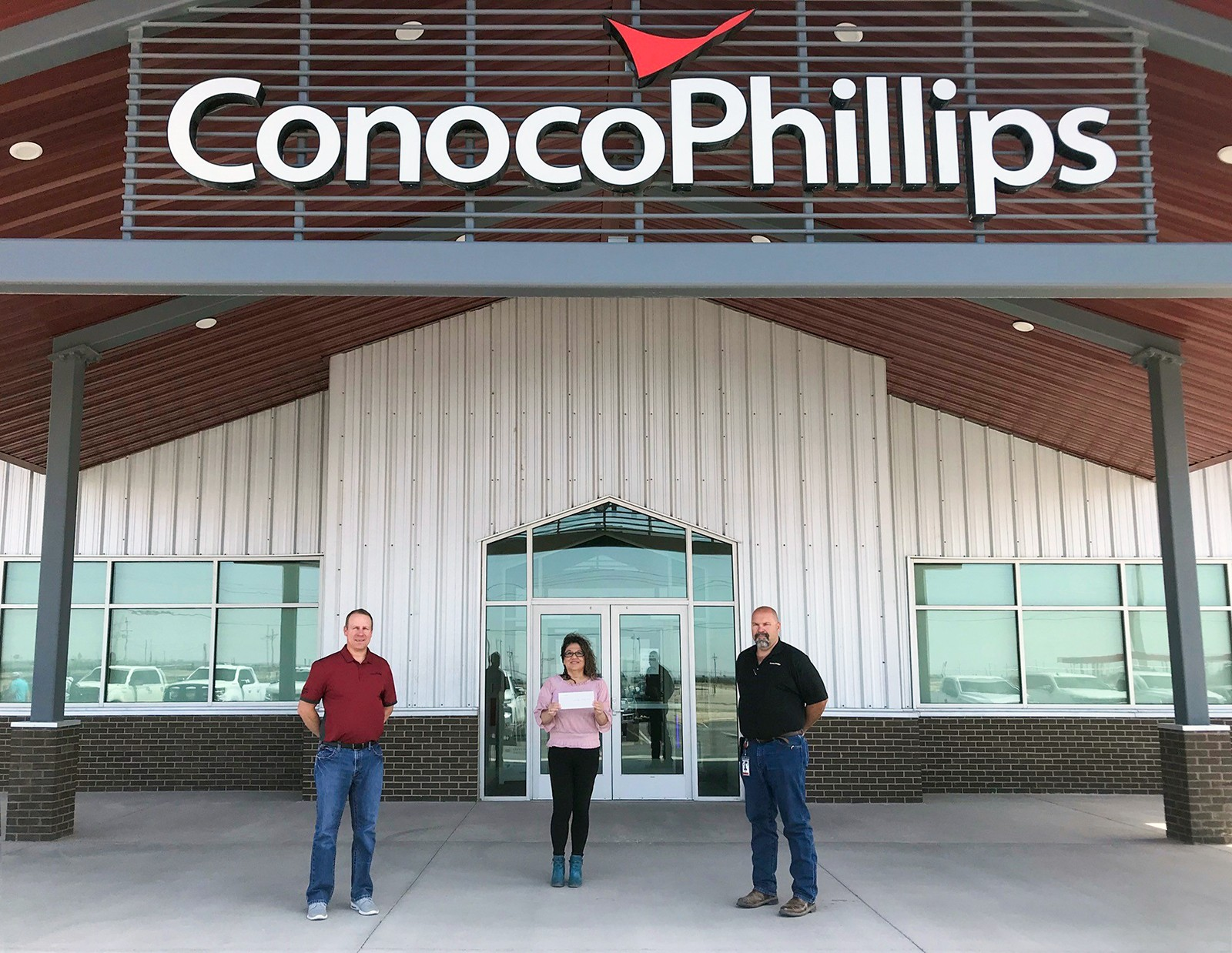 Three people standing outside entrance of ConocoPhillips New Mexico office