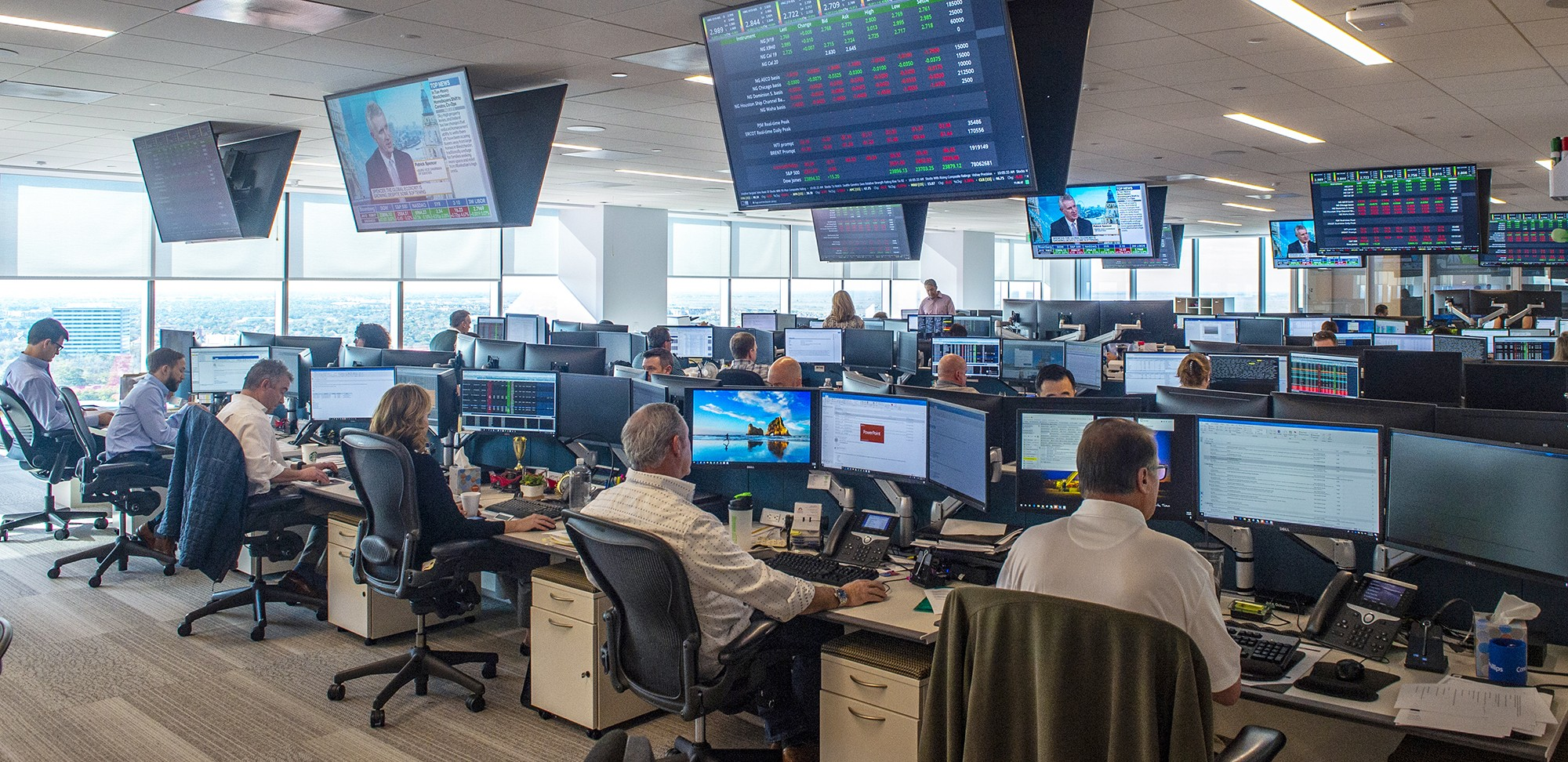 Commercial floor - room with workers at computers and ceiling monitors