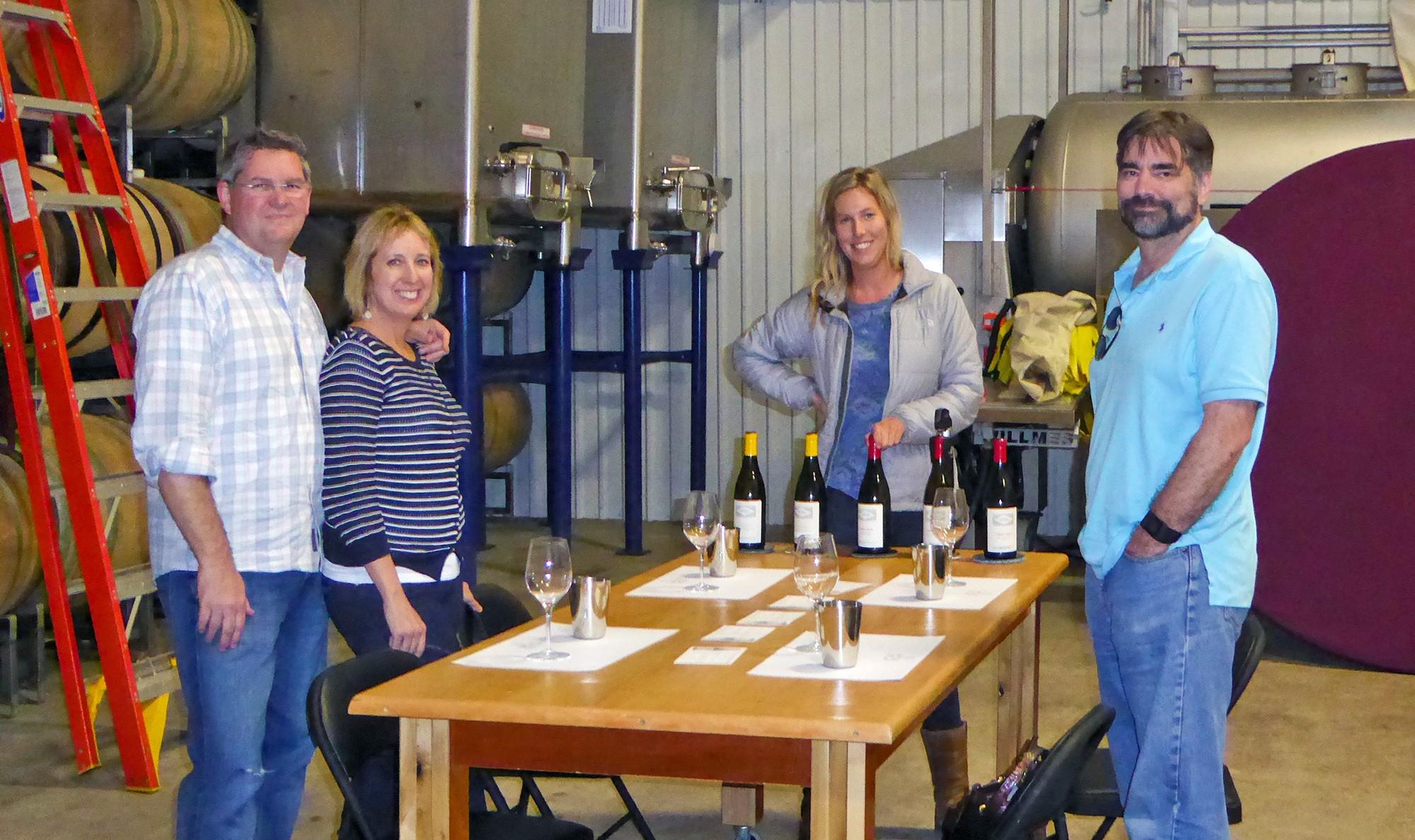 4 people among wine making equipment