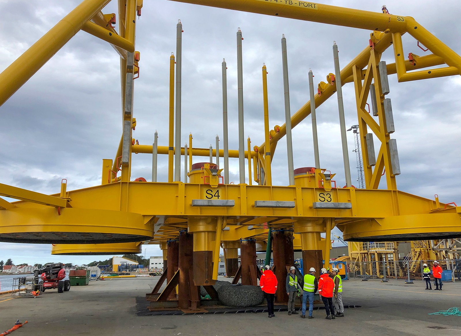 group of workers gathered in front of large yellow metal structure